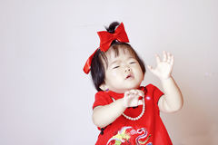 Chinese little baby in red cheongsam scared by soap bubbles. Cute Chinese little baby, 1 year old, wear red cheongsam and with red silk bow on her hair, wear Royalty Free Stock Photos