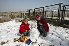 A Chinese little boy making a snow man with mom in winter season Stock Photo