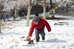 A Chinese little boy playing his toy track in the snow field in winter season Stock Images