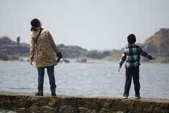 A Chinese little boy watching the sea with mom on the beach Royalty Free Stock Photography