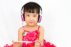 Chinese little girl on headphones holding mobile phone Stock Images