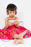 Chinese little girl on headphones holding mobile phone Royalty Free Stock Photography