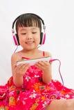 Chinese little girl on headphones holding mobile phone Stock Photo