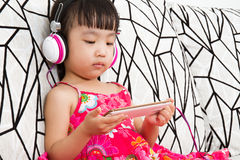 Chinese little girl on headphones holding mobile phone Stock Photos