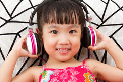 Chinese little girl on headphones holding mobile phone Royalty Free Stock Photo