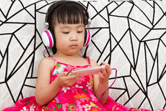 Chinese little girl on headphones holding mobile phone Royalty Free Stock Image