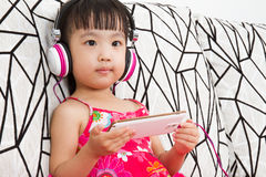 Chinese little girl on headphones holding mobile phone Stock Photography