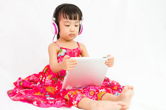 Chinese little girl on headphones holding tablet Stock Photo