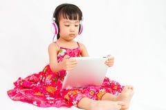 Chinese little girl on headphones holding tablet Stock Photo