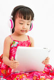 Chinese little girl on headphones holding tablet Royalty Free Stock Photo