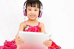 Chinese little girl on headphones holding tablet Stock Photos