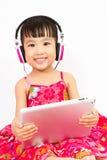 Chinese little girl on headphones holding tablet Stock Image