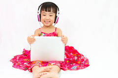 Chinese little girl on headphones holding tablet Royalty Free Stock Photography