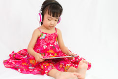 Chinese little girl on headphones holding tablet Stock Images