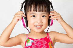 Chinese little girl on headphones Royalty Free Stock Photos