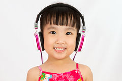 Chinese little girl on headphones Royalty Free Stock Image