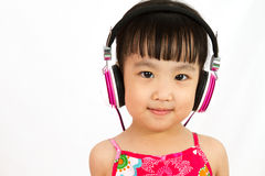 Chinese little girl on headphones Royalty Free Stock Images
