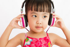 Chinese little girl on headphones Stock Image