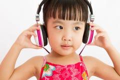 Chinese little girl on headphones Stock Image