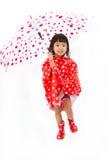 Chinese Little Girl Holding umbrella with raincoat Royalty Free Stock Photo