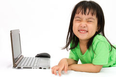 Chinese little girl lying down with laptop Stock Photography