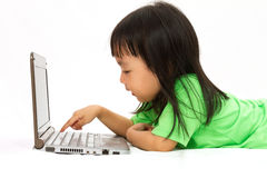 Chinese little girl lying down with laptop Royalty Free Stock Photography