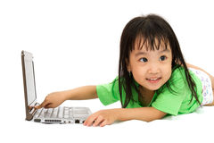 Chinese little girl lying down with laptop Royalty Free Stock Images