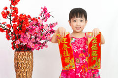 Chinese little girl pising holding Spring festival couplets. Greeting for Chinese New Year in isolated white background royalty free stock image
