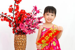 Chinese little girl pising holding Spring festival couplets. Greeting for Chinese New Year in isolated white background royalty free stock photos