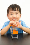 Chinese little girl pushing a toy shopping cart Stock Image