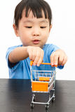 Chinese little girl pushing a toy shopping cart Stock Photo