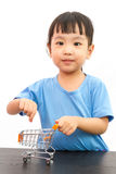Chinese little girl pushing a toy shopping cart Stock Photography
