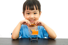 Chinese little girl pushing a toy shopping cart Royalty Free Stock Photography