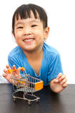 Chinese little girl pushing a toy shopping cart Royalty Free Stock Image