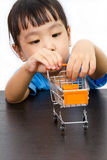 Chinese little girl pushing a toy shopping cart Stock Photos