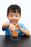 Chinese little girl pushing a toy shopping cart Royalty Free Stock Images