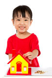 Chinese Little Girl Puts Coins into Piggy Bank Royalty Free Stock Photo