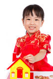 Chinese Little Girl Puts Coins into Piggy Bank Stock Photography
