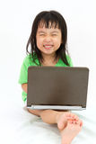 Chinese little girl sitting on floor with laptop Stock Photos
