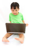 Chinese little girl sitting on floor with laptop Royalty Free Stock Image