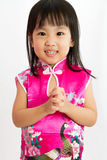 Chinese Little Girl wearing Cheongsam with greeting gesture Stock Image