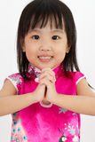 Chinese Little Girl wearing Cheongsam with greeting gesture Royalty Free Stock Image