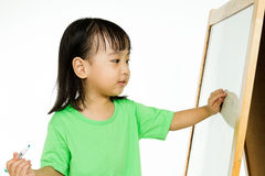 Chinese little girl writing on whiteboard Royalty Free Stock Photography