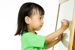 Chinese little girl writing on whiteboard Stock Images