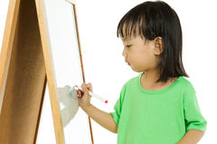 Chinese little girl writing on whiteboard Royalty Free Stock Photos