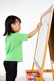 Chinese little girl writing on whiteboard Stock Photo