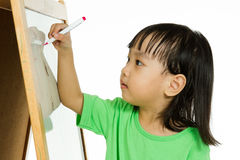 Chinese little girl writing on whiteboard Royalty Free Stock Images
