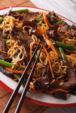 Chinese lo mein with beef, muer and vegetables close-up. vertica Royalty Free Stock Photo