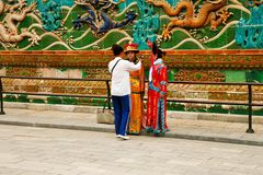 Beijing, China, 06/06/2018 Two Chinese girls in national costumes are photographed near the Wall of Nine Dragons in the Forbidden royalty free stock photo