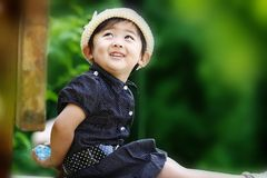 Chinese lovely girl. The Chinese girl with white hat was hiding the bottle and smiling look toward her mater. This photograph was taken in her 26 months Royalty Free Stock Images
